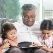 Grandfather and granddaughter using modern technology — Stock Photo #79645906