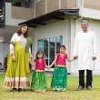 Indian family holding hands outside new home — Stock Photo #82194424