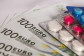 Medicine tablets on money — Stock Photo