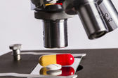 Microscope and pills — Stock Photo