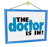 The Doctor Is In words on office window sign — Stock Photo