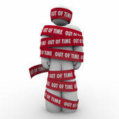 Out of Time on red tape wrapped around a man — Stock Photo