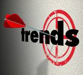 Trends word on a wall with bulls-eye and arrow hitting the target — Stock Photo