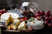 Cheese plate served with wine, jam and honey — Stock Photo