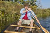 Senior male paddling canoe — Stock Photo