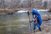 Senior paddler carrying a packraft — Stock Photo