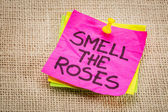 Smell the roses reminder note — Stock Photo