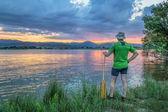Каноэ гребца наблюдая закат — Стоковое фото