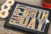 Happy birthday on tablet with tea and cookies — Stock Photo