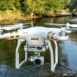 Постер, плакат: Phantom quadcopter drone flying over river