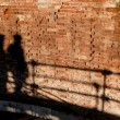 People walking, casting shadows on a wall — Stock Photo #68359283