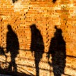 People walking, casting shadows on a wall — Stock Photo #68359287