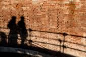 People walking, casting shadows on a wall — Foto de Stock