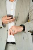 Businessman using the Apple Watch and an Apple iPhone 6 — Stock Photo