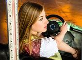 Beautiful girl in an electric bumper car at amusement park — Stock fotografie