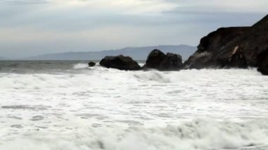Moderate Wide Shot Of Waves Hitting Headland Rocks — Stock Video