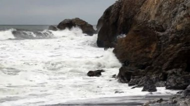Tight Shot Moderate Waves Crashing Into Rocky Headlands — Stock Video