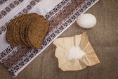 Rye bread, egg and salt on canvas — Stock Photo