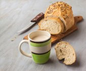 Loaf of rye bread and cup of milk — Stock Photo