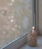 Window with burning candle — Stok fotoğraf