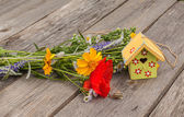 Decorative starling house and bouquet of flowers — Stock Photo
