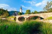 Church of Sv. John the Baptist and a bridge by the Bohinj lake — Stock Photo
