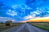 Sunset over rural road and hay bales — Stock Photo