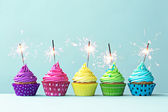 Colorful cupcakes with sparklers — Stock Photo