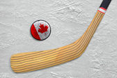 Hockey stick and puck on the Canadian hockey rink — Stock Photo