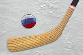Hockey stick and puck on the Russian hockey rink  — Stock Photo