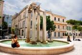 Unidentified tourists near fountain on the square of Assas, Nimes, France — Stock Photo