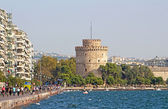 White Tower and unidentified people are walking on the embankment in a storm in Thessaloniki, Greece — Stock fotografie
