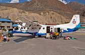 JOMSOM, NEPAL - OCTOBER 05, 2008: Passengers arrived and unloaded luggage from the plane of Sita airlines at the Jomsom airport, Annapurna region, Nepal — Stock Photo