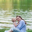 Pregnant woman and her son 2 yo on the green grass. Concept of motherhood — Stock Photo #59310827