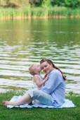 Pregnant woman and her son 2 yo on the green grass. Concept of motherhood — Stock Photo
