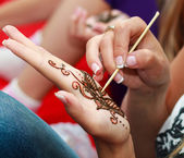 European woman applying henna tattoo — Stock Photo