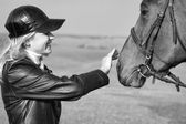 Horsewoman stroking the horse's head, Black and White — Stock Photo