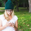 Beautiful casual woman texting on her cell phone — Stock Photo #52910541
