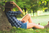 Cowgirl lies on field relaxing and enjoy the nature — Stock Photo