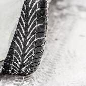Winter tyre on snowy road — Stock Photo