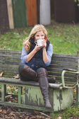 Smiling fashionable blonde drinking coffee or tea outdoors — Stock Photo
