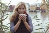 Smiling fashionable blonde drinking hot beverage — Stock Photo