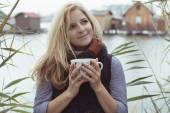 Smiling fashionable blonde drinking hot beverage — Foto de Stock