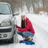 Woman putting winter tire chains on car wheel snow breakdown — Stock Photo