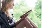 Woman lying in a garden and enjoying book reading — Stock Photo