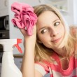 Concentrated woman cleaning the bar in kitchen — Stock Photo #64811329