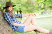 Cute cowgirl resting under the tree — Stock Photo