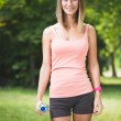 Beautiful young fitness woman holding water after working out — Stock Photo #77909652