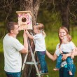 Happy family with Wooden birdhouse — Stock Photo #63884403
