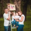 Happy family with Wooden birdhouse — Stock Photo #63884689